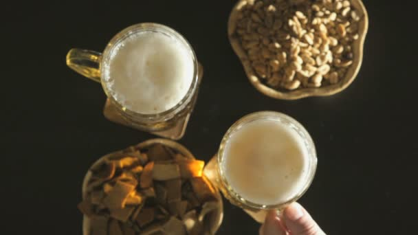 Two hands with a light beer in beer mugs