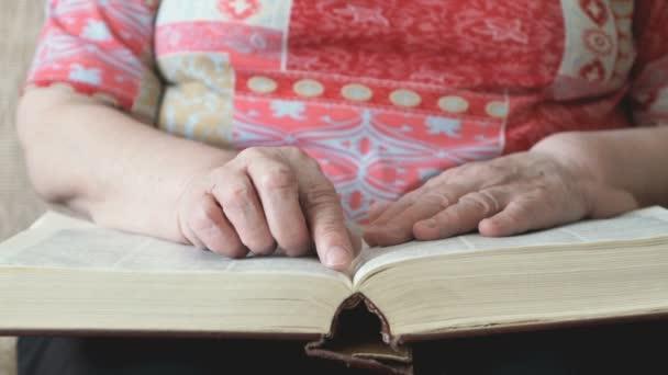 Stará žena čtení stránek tlusté knihy