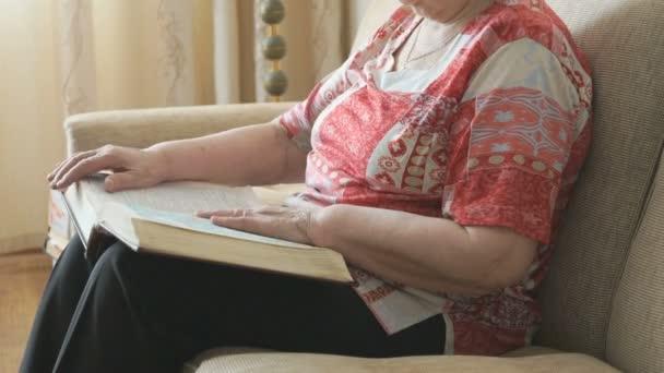 Stará žena listoval stránkami tlusté knihy
