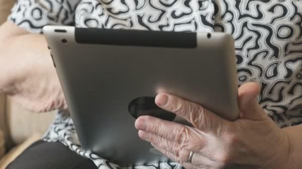 Stará žena se dívá na informace o digitálním tabletu