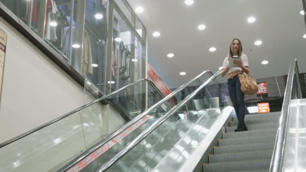Stylové módní dívka jede na eskalátoru