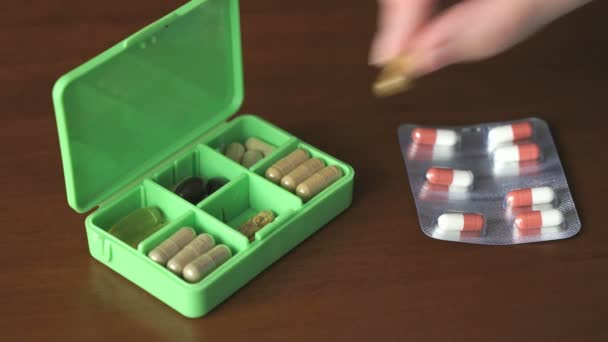 Hand puts tablets in a container for tablets