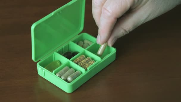 Hand puts pills in a container for tablets