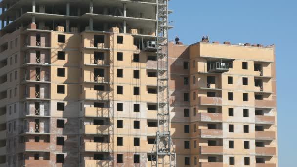 Dělníci pracují na staveništi. Jeřáb