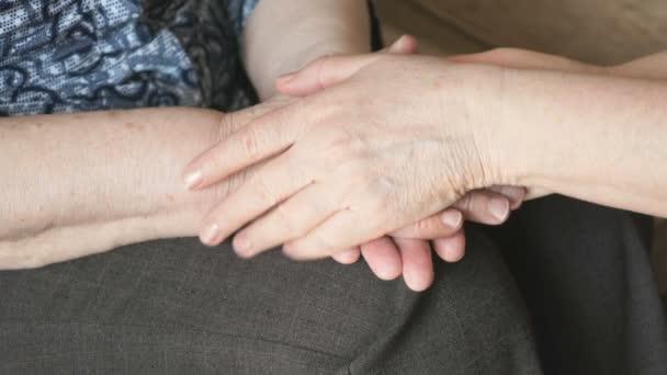 Frau streicht über eine alte faltige Frauenhand