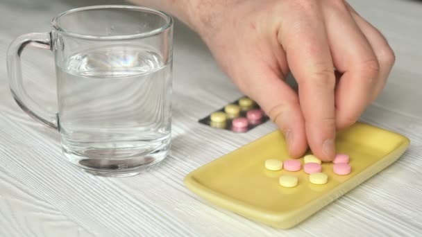 Mans hand takes the pills from a yellow container