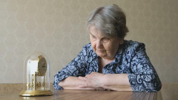 Stará žena se dívá na stolní hodiny s kyvadlem