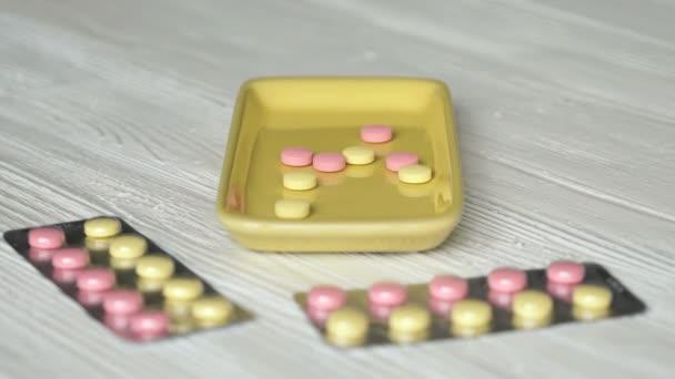 Hand nimmt Tabletten in Behälter auf den Tisch