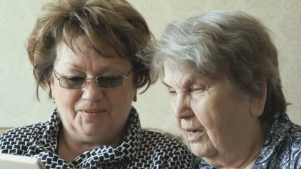 Dvě starší ženy dívat obrázků pomocí tablet