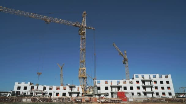 Three construction cranes working on the site