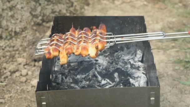 Vaření párků na uhlí na grilu