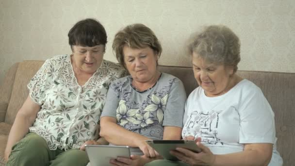 Elderly women looking photos using digital tablets