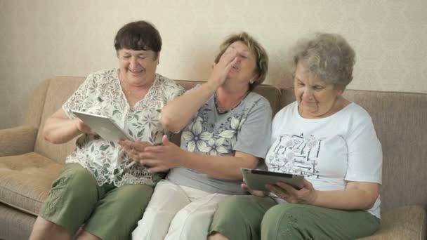 Starší ženy při hledání fotografií pomocí digitálních tablety