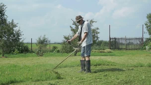 Gärtner mäht das Gras mit Rasentrimmer