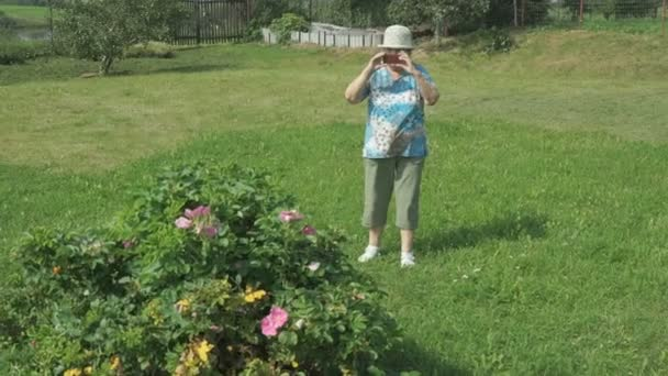 Elderly grandmother takes photos the park