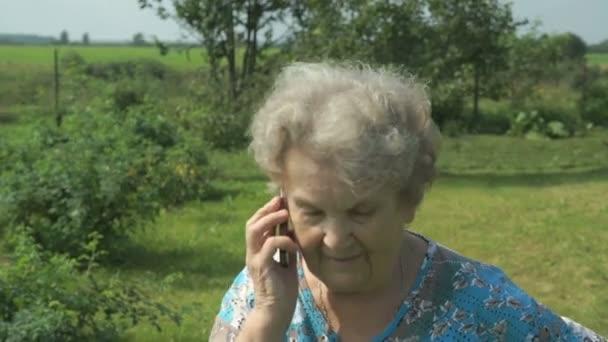 Starší žena 80s komunikuje mobilní telefon venku