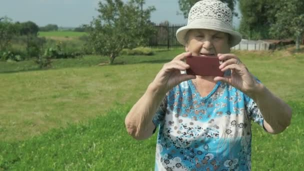 Aged woman taking photos the nature of park
