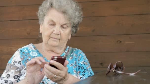 Alte Frau am Tisch hält Smartphone in der Hand