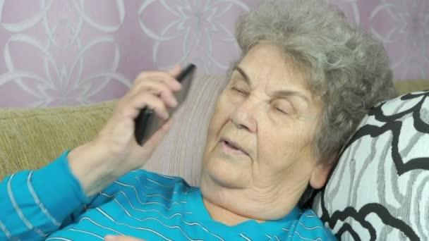Seniorin telefoniert mit Smartphone im Zimmer