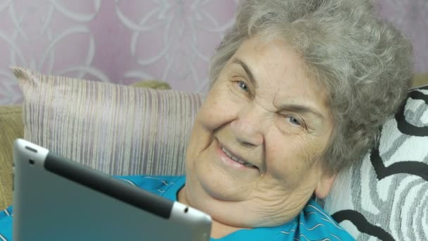 Stará žena drží tabletový počítač uvnitř