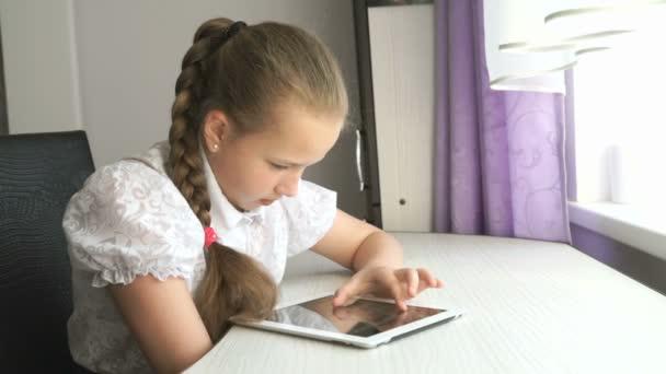 Školačka používá digitální tabletový počítač doma
