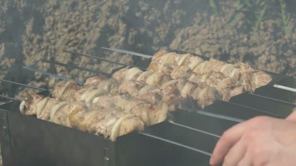 Vaření vepřového masa na kovové špejle na uhlí