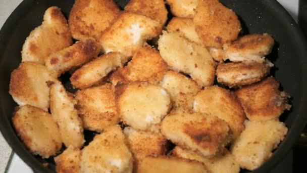 Batter-fried chicken meat nuggets is cooked on pan