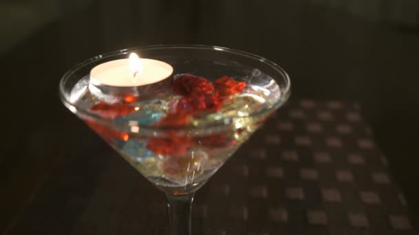 Burning candle in a glass scattered gemstones. Offer hands and hearts