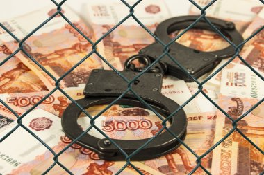 Metal handcuffs on the background of Russian rubles under wire netting (lattice)