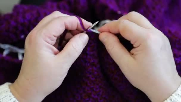 Womens hands knit woolen jacket with knitting needles. Top view, close-up of hands and knitting.