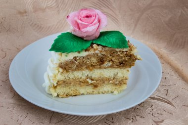 piece of sponge cake that is decorated with sugar rose