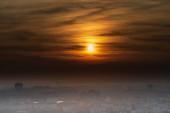 Slunce s barevným panoramatem nad Ostravou z kopce Halda Ema v České republice během podzimního mlhavého dne