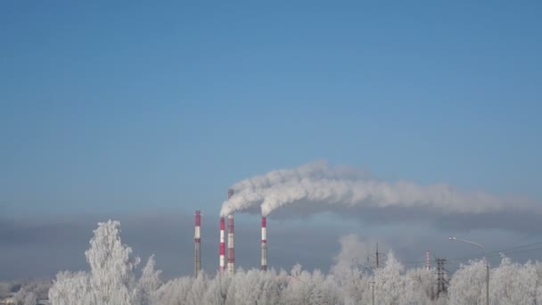 Bílý kouř z komína továrny v dálce