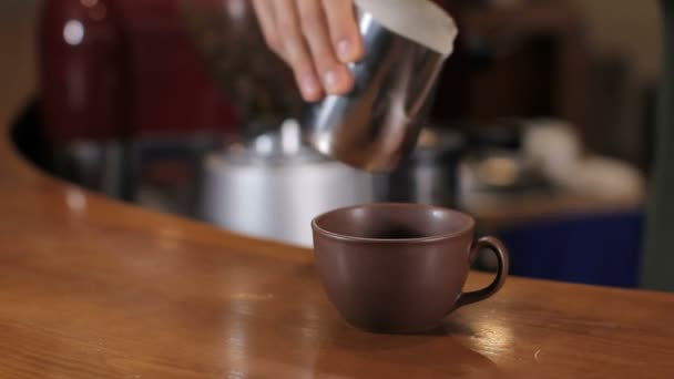 Bartender pouring milk in cup of cappuccino. Close up