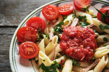 Penne pasta in tomato sauce with chicken, tomatoes decorated  parsley