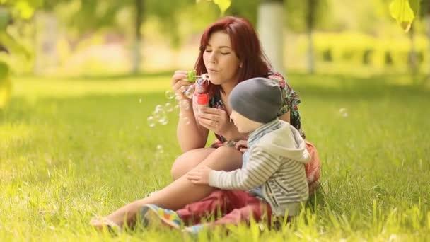 Mladá matka a dítě foukat bubliny