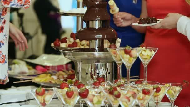 Lidé ponoří jahody v čokoládové fontáně. Oslava