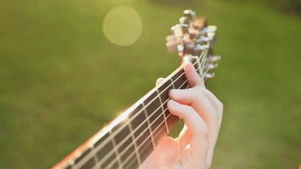 Holka hraje kytara, kytara close-up hmatník