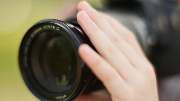 Hände kleines Mädchen macht Fotos mit der Kamera. Hand dreht das Objektiv aus nächster Nähe.