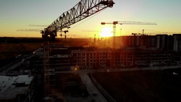 Siluety stavebních jeřábů při západu slunce. Video Drone.