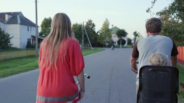Fiatal pár biciklizik a kislányukkal naplementekor..
