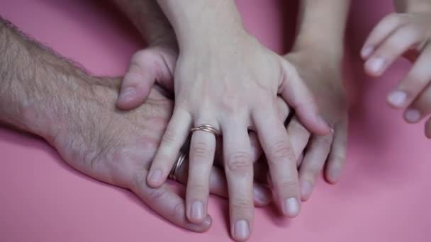 Als Zeichen des gemeinsamen Erfolgs vor rosafarbenem Hintergrund schließt sich eine befreundete Familie zusammen..