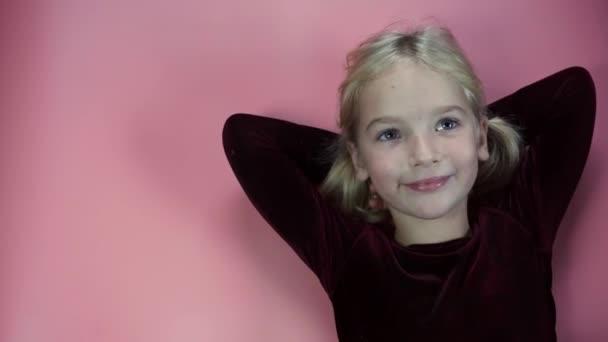Portrét ležící malé sedmileté dívky na růžovém pozadí.