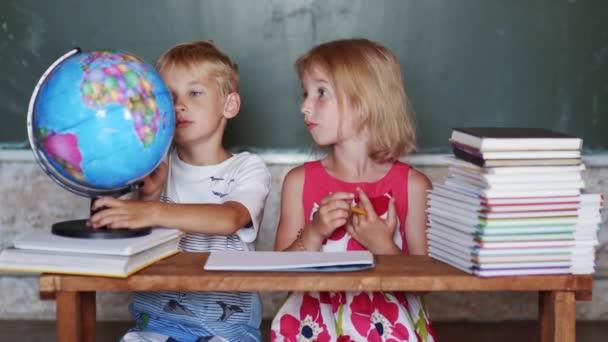 Bratr a sestra studují doma se světovou zeměkoulí.