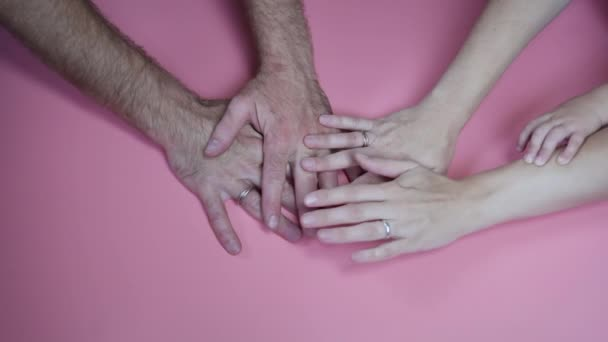 A friendly family join their hands as a sign of joint success against a pink background.