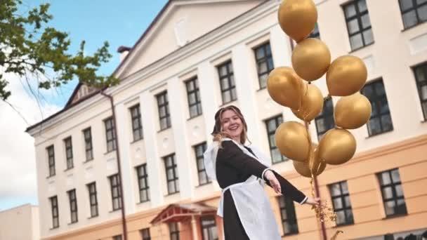 Šťastná ruská školačka s balónky v den promoce.