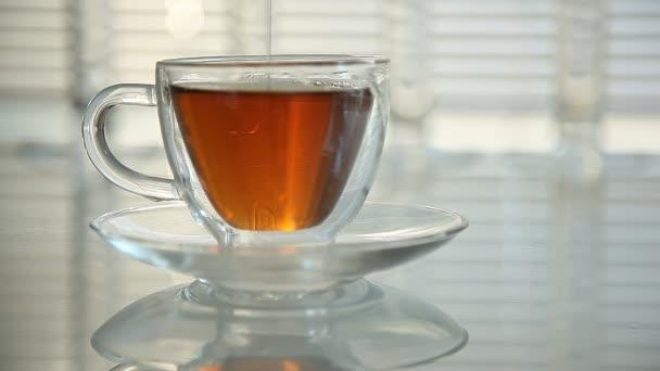 med se nalije do šálku čaje. detail