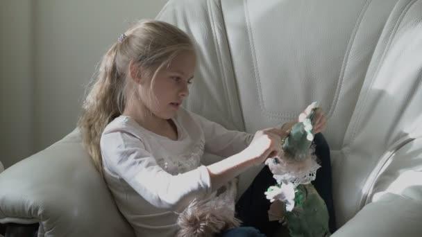 Rozkošná holčička hraje ve svém pokoji s panenkou