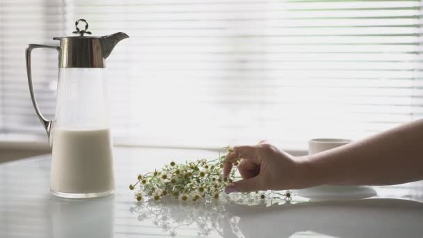 a bouquet of daisies and a cup of coffee on the table