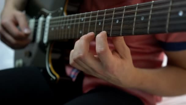 Young man playing on guitar. close up